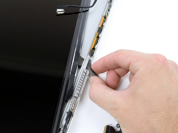 Carefully guide the LCD cable through the slot in the rear display bezel.