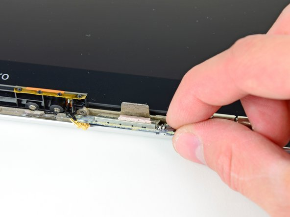 Image 1/2: Before installing a new AirPort card, be sure the thermal material on its surface is intact and aligned with the small heat sink on the display frame.