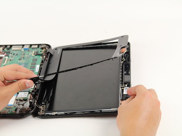 Image 1/2: Remove the panel slowly to prevent damaging the screen connectors. An adhesive strip holds the bottom edge of the screen casing in place.