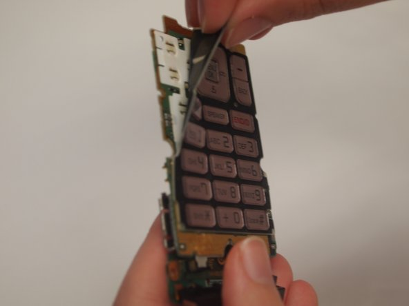 Carefully peel the rubber keypad mat off of the motherboard. The keypad is secured with an adhesive material, so there will be slight resistance.