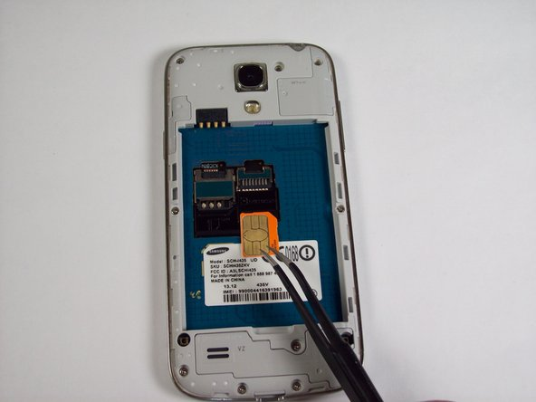 Using tweezers, remove the SIM card by sliding it towards the bottom of the device.
