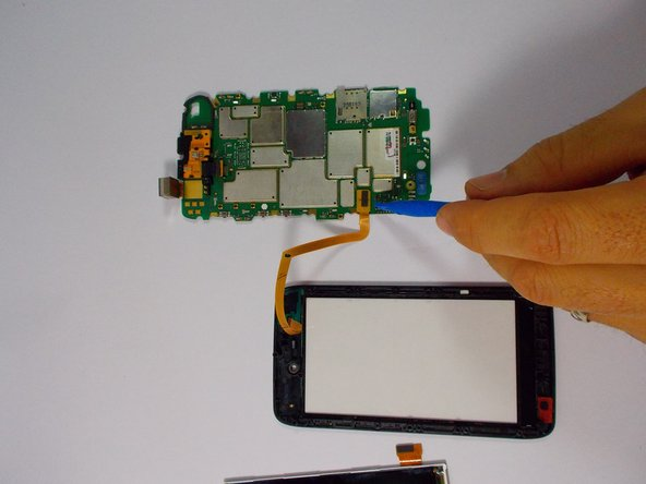Image 2/2: With the LCD display removed, remove the ribbon cable connecting the touchscreen to the motherboard