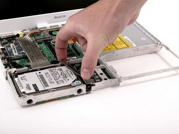 Lift the metal restraining bracket from the hard drive and place it aside.