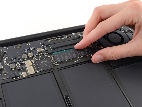 Image 1/2: Don't lift the SSD more than half an inch—doing so may damage the SSD or its socket on the logic board.