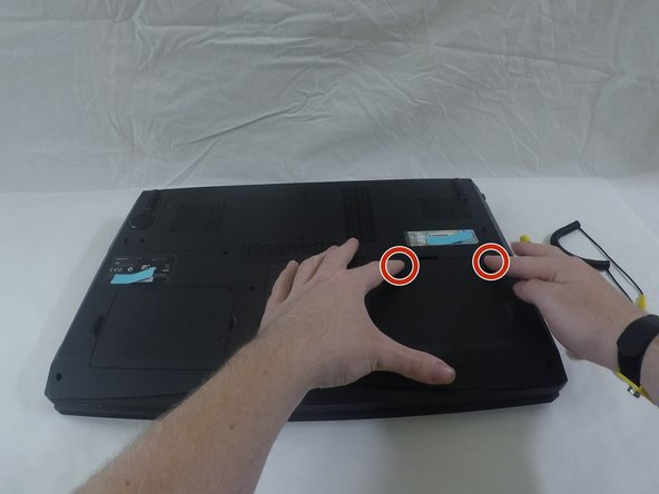 Image 1/2: Push both locking tabs inward, one is spring loaded and you will have to hold it while you remove the battery.