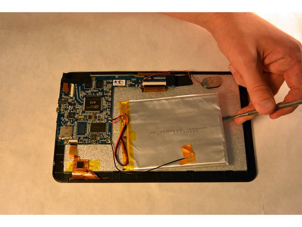 Gently remove the battery from the tablet by sliding the metal spudger under the battery.