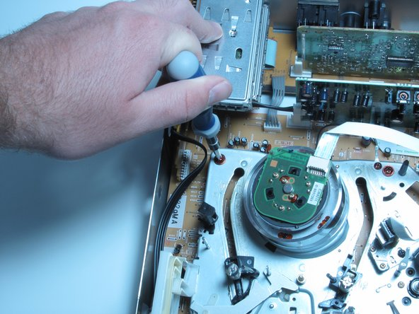 With the device front facing you remove the six screws with a phillips head screwdriver around the VHS drive.