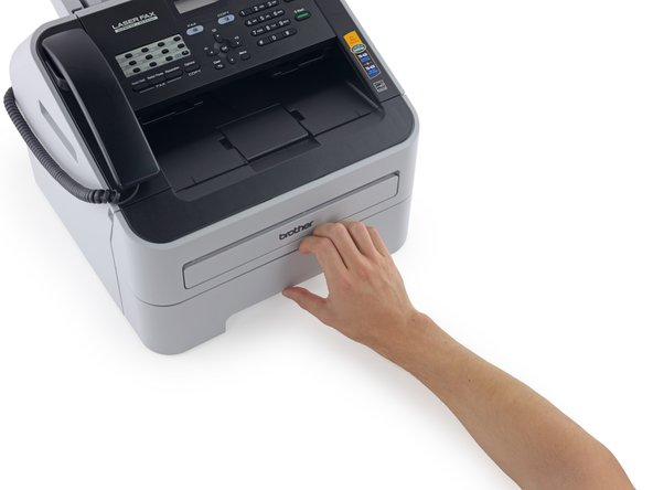 Image 1/2: Continue pulling until the paper tray is free of the fax machine.