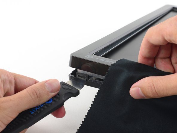 While pressing the clip in, pull up on the lower edge of the bezel. The entire corner should pop free.