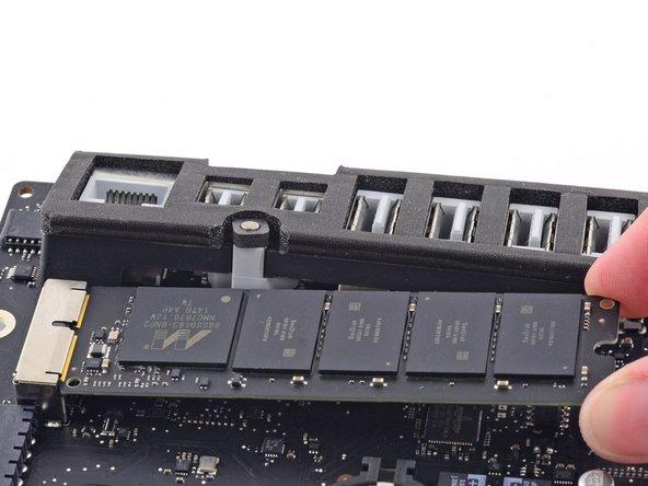 Hebe die SSD an der Seite ganz rechts etwas an und ziehe sie gerade aus ihrem Anschluss auf dem Logic Board heraus.