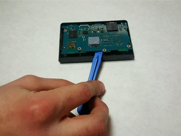 Use a plastic opening tool to pry up gently on the motherboard, and remove it.