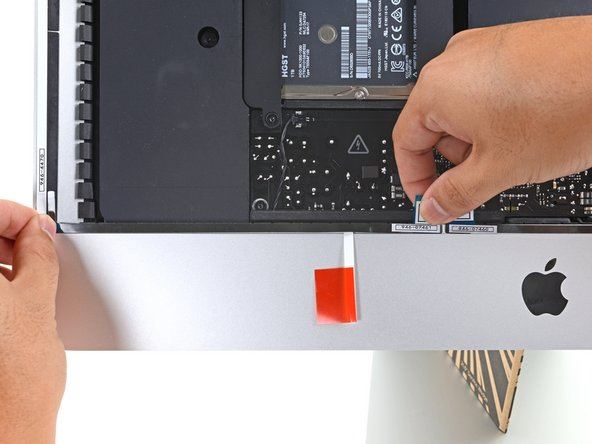 Repeat the previous steps for the 4L adhesive strip, placing it along the bottom left edge of the iMac.