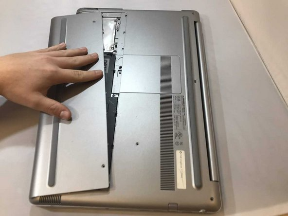 Apply pressure using your fingertips on the top of the cover, pushing to the front of the laptop. This will make the plate slide off exposing the hard drive.
