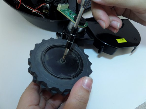 Unscrew the black 1 cm screw securing the center of the wheel.