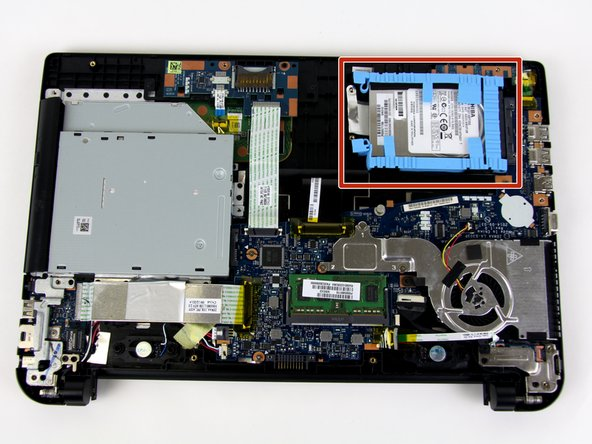 The hard drive is held in place with a soft, blue rubber retainer. The retainer can be disconnected by pulling up on the two tabs at the left side of the hard drive in these images.