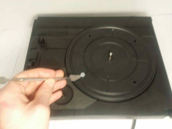 Remove the 4 rubber plugs which hold the turntable platter in place