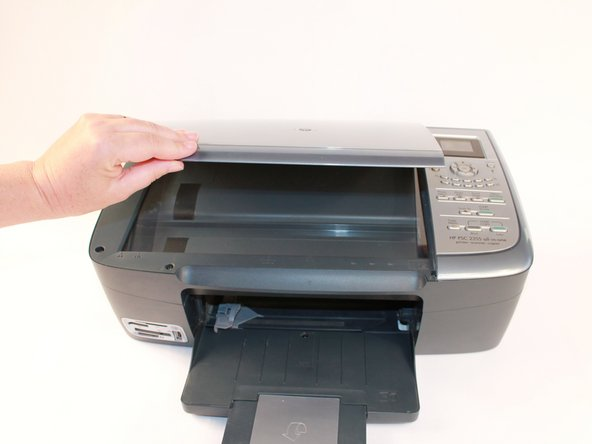 Grasp the scanner lid cover from the front of the device and lift lid all the way up until it stands on its own.