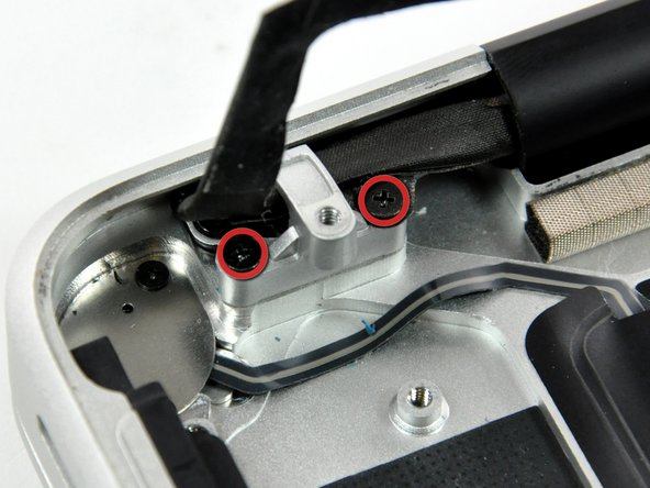 Image 1/2: Remove two 8 mm Phillips screws securing the camera cable bracket to the upper case.