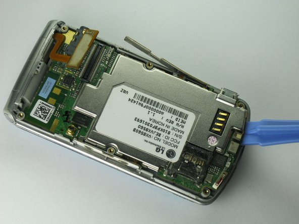 Carefully insert the plastic opening tool between the motherboard and the back of the phone.