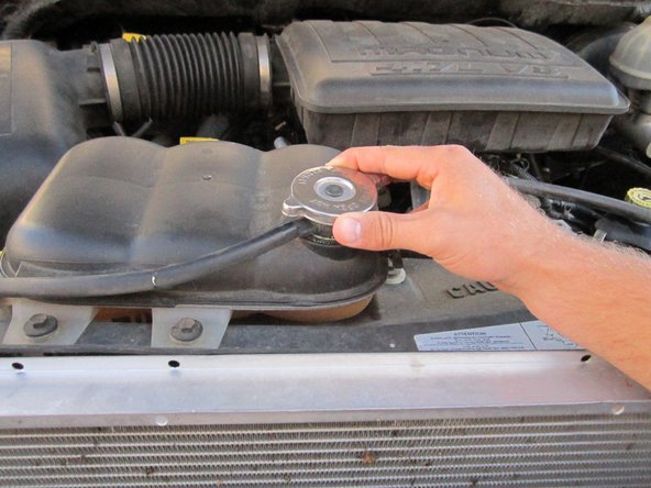 Locate the coolant reservoir cap and remove it by pressing down and turning it counterclockwise.