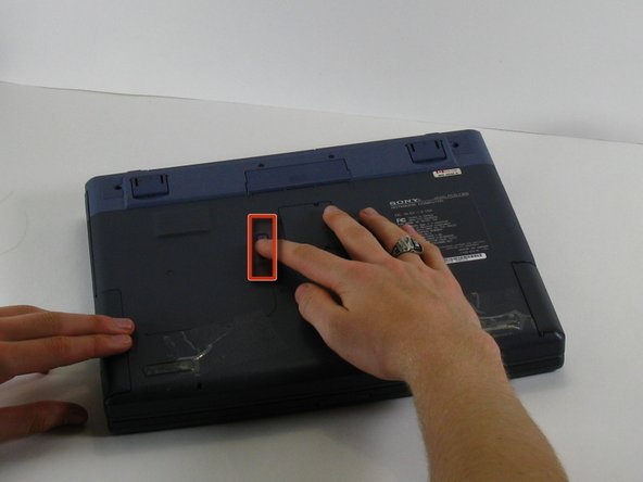 Image 1/2: With your other hand, pull the floppy drive out of the floppy drive bay.