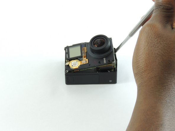 Insert a metal spudger between the back plastic housing and the camera board assembly. Working around the edge to be careful of the inner components, carefully remove the camera.