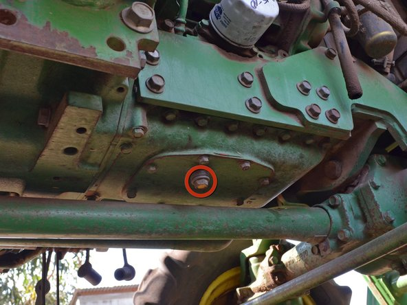 The drain plug is a 17 mm hex bolt located on the underside of the tractor.