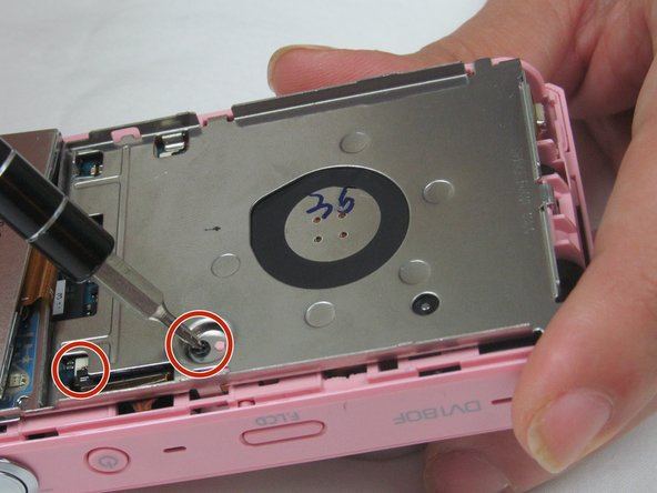 Use a Phillips screwdriver to remove the two small screws holding the outer casing to the mother board.