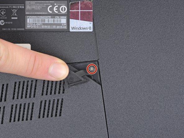 Remueve el tornillo de 5.3 mm Phillips #00 que sujetan la puerta de acceso RAM.