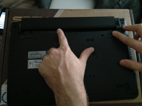 Image 2/2: Slide the standard switch toward the center of the laptop.  Hold the spring-loaded switch in the same position (pressed towards the center of the laptop) and, while depressed, disconnect the battery.