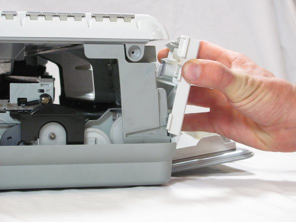 Inside the printer is a small white tab. Press it inward with a spudger until a pop is heard.