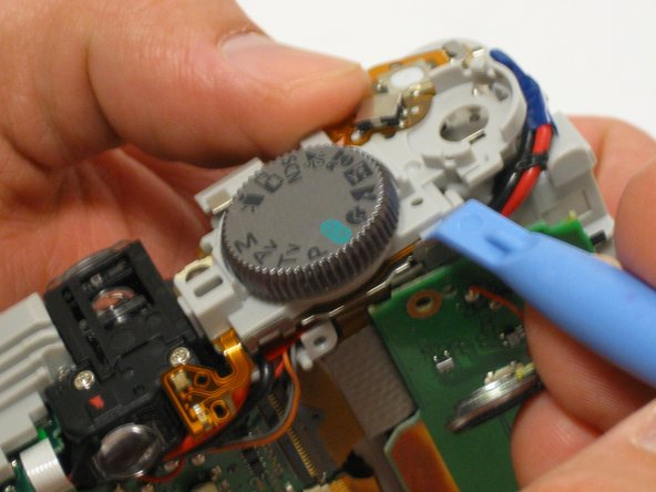 Use the plastic opening tool to begin separating the user button circuit board from the shutter button and settings dial housing unit.