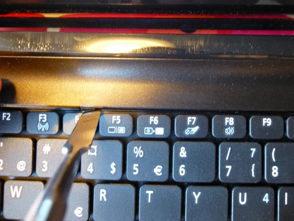Image 2/2: Then move down along the sides where there is one pin on each side. After that twist the keyboard towards you.