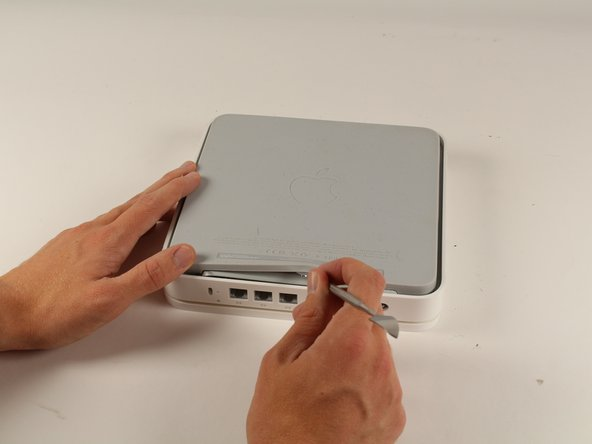 Turn the device upside down to reveal the rubber section of the back plate. Using a metal spudger, carefully wedge the blunt tip into the space between the aluminum back plate and the rubber, separating the two pieces.