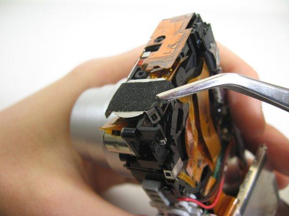 Lift up tape slightly on both sides of speaker.