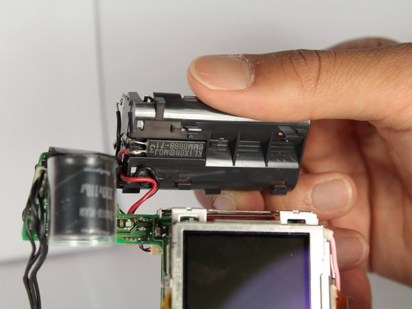 Image 2/3: The battery compartment should now be detached from the rest of the motherboard unit.