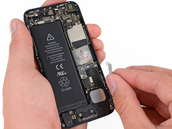 Image 2/2: Remove the metal battery connector bracket from the iPhone.