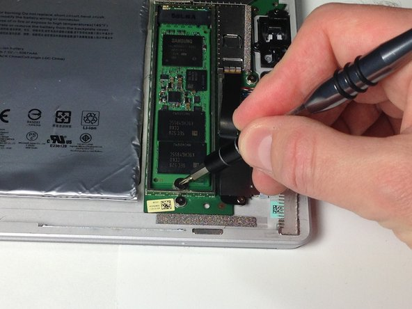 Remove the 1.0 mm Torx T4 screw holding down the SSD drive.