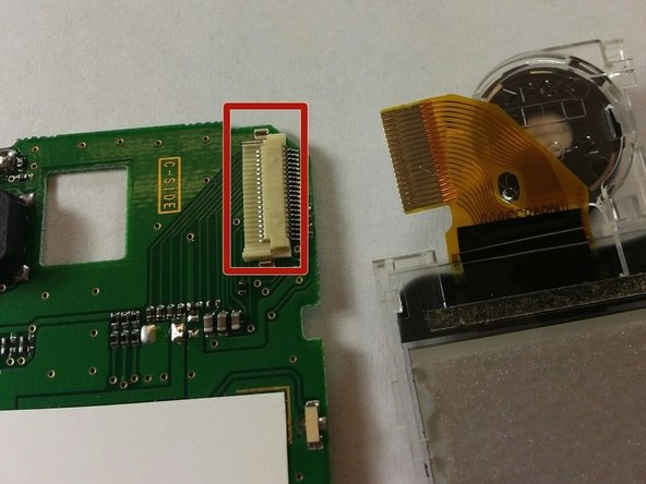 Remove the attached ribbon from the circuit board by prying open the gray plastic clip at the top right of the circuit board.