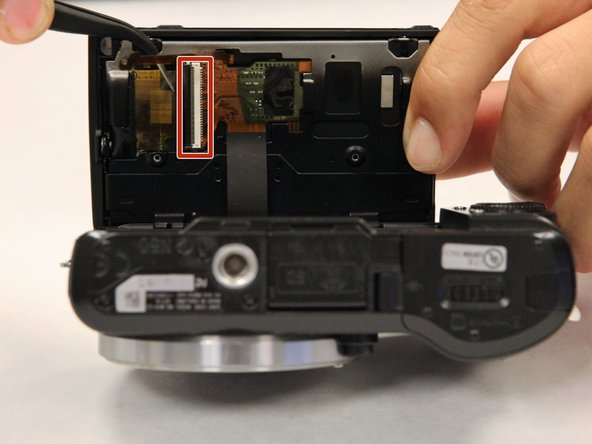Using tweezers, gently pull up and away on the ribbon cable connected to the motherboard, after which, the LCD screen should come off.
