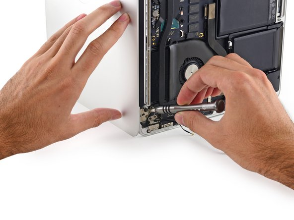While holding the display with your left hand, remove the remaining T8 Torx screw from the upper display bracket.