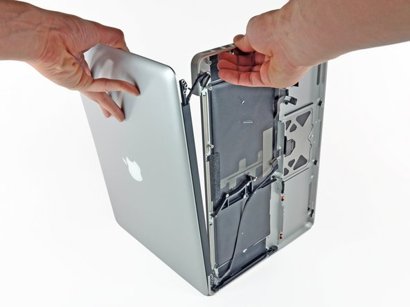 Lift the display away from the upper case, minding any brackets or cables that may get caught.
