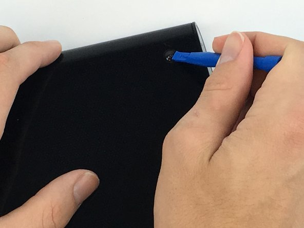Image 2/2: Use a plastic opening tool to remove the two rubber grips on the back of the tablet.