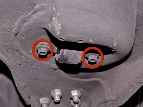 Locate the two 10 mm hex bolts securing the bottom of the shock to the lower control arm. They are on the underside of the lower control arm.