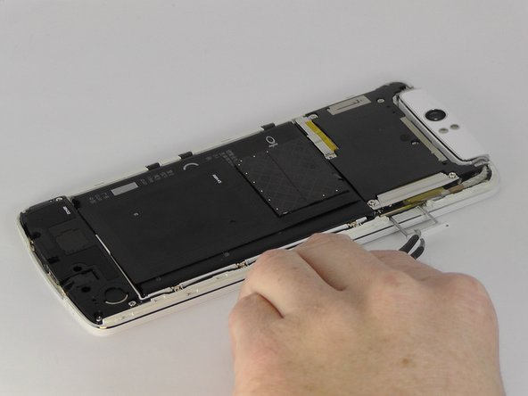In the first photo we rotated the phone 180 degrees. Use tweezers to remove the SIM card tray.