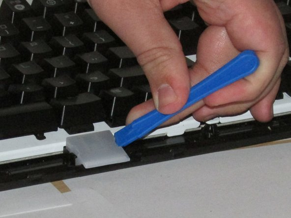 Using a plastic opening tool, lift the plastic covering  away from the LED light.