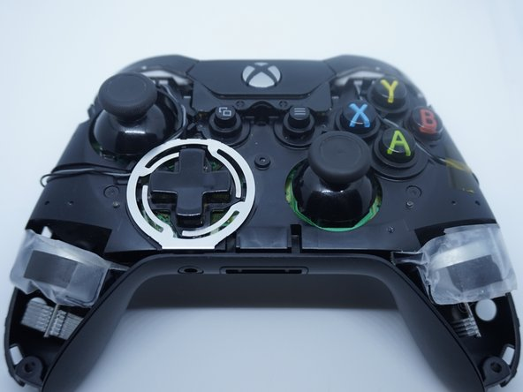 With the screws removed from the back, flip the controller to the front. Remove the front plastic cover.