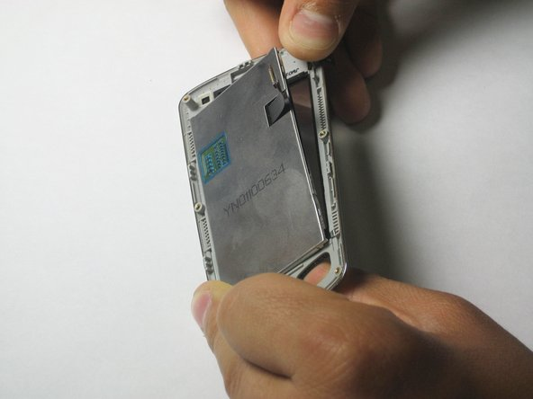 Image 1/2: In the next step, be gentle while removing the LCD screen. If you jerk the LCD screen off, it may crack, so be careful and slowly peel away the adhesive.
