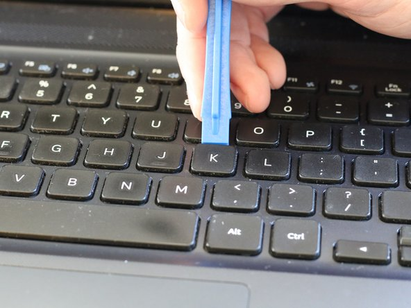 Locate the unresponsive/sticky key. With the opening tool, begin to lever the key off of the keyboard.