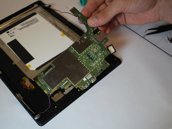 Remove the tablet's Motherboard by lifting it up with your hands.